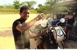 A Brazilian local helps Freund fill his gas tank by simply unzipping the Fandango Pro Tank Bag from the included harness that is securely strapped to his Kawasaki KLR 650